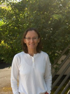 Informal portrait of a middle aged woman wearing glasses and button up white shirt; tree and dirt road behind her.