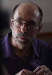 Informal portrait of a bearded middle aged man wearing glasses and a purple button down shirt.